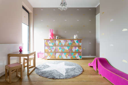 Cosy girl's room with beautifully decorated chest of drawers and a round fluffy carpet on the wooden floor Reklamní fotografie - 61585049