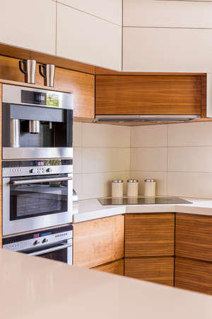 cooktop: Cosy kitchen arranged in warm colours, with a set of ovens and an electric cooktop