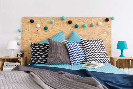 nightstands: Close-up of a decorated bed with a backboard made of particle board and nightstands of wooden boxes Stock Photo