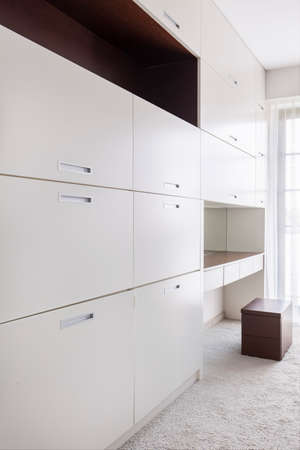 cabinets: Large closet with white cabinets in a very bright interior Stock Photo