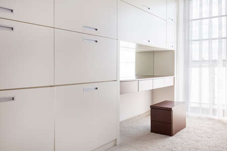 fitted: Very bright dressing room with large white cabinets and a vanity with drawers