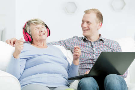 grandsons: Shot of a happy senior woman listening to the music while her grandson is sitting next to her