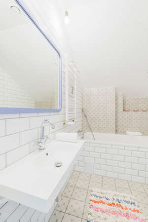 chromium plated: Minimalist bathroom in white, brick-resembling tiles, with a rectangular sink and a bathtub Stock Photo