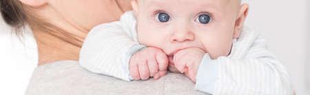 Junge Mutter saugen Daumen blauäugigen Baby Standard-Bild - 61583380