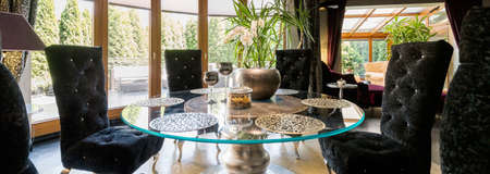 dining table and chairs: Glass dining table and black velour quilted chairs Stock Photo