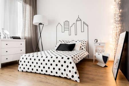 Elegante interior de dormitorio con muebles blancos y sábanas de puntos en la cama Foto de archivo