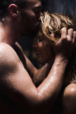 cuerpos desnudos: Hombre atlético hermoso que besa y abraza a la mujer hermosa en la ducha