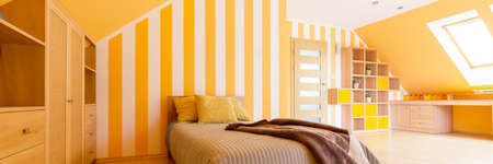 Panoramic shot of a youth room with orange and white stripes on the wall