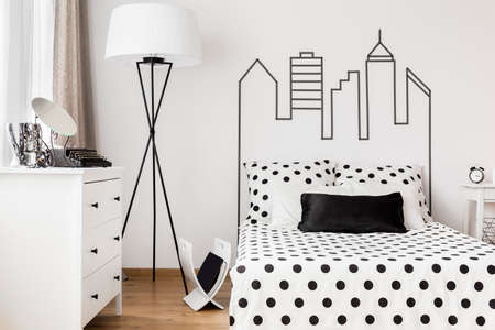 Vrouwenslaapkamer in zwart-witte kleuren met het bed en commode Stockfoto