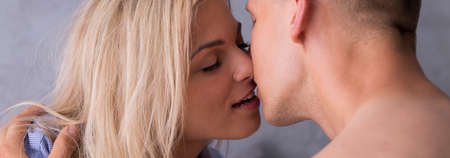eroticism: Woman in a male shirt and a man are passionately kissing