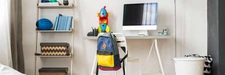 mathematician: Pupil home workplace with minimalistic desk, toys and rucksack on chairs back Stock Photo