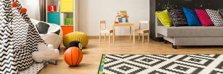Colorful child room interior with teepee, bean bag chair and mosaic theme carpet