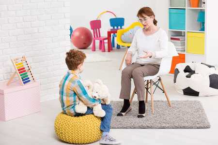 troublesome: Therapy session classroom with boy listening the woman psychologist speech