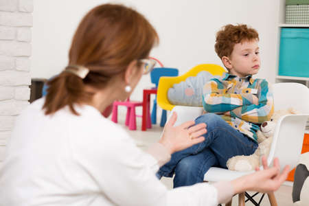 Woman therapist talking to the boy sitting on a chair with his arms folded