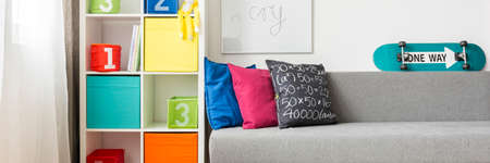 furniture home: Room corner with a rack with colorful boxes and skateboard located on a sofa Stock Photo