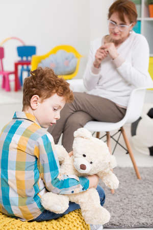 unbearable: Autistic child holding a teddy bear with his therapist at the background Stock Photo