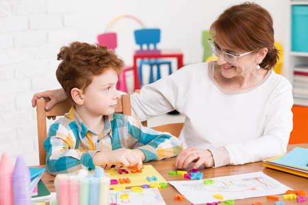 Terapeuta de la mujer que se sienta en un escritorio, cerca del niño