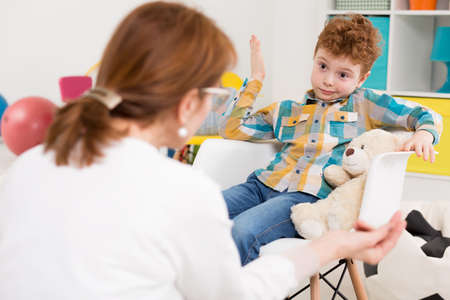 troublesome: Boy sitting laid-back on the chair in front of his psychologist