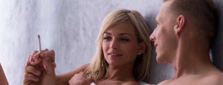 eroticism: Man gives a woman a lit cigarette while the are lying in bed
