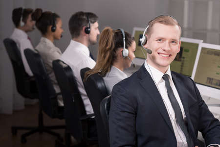 selling service: Smiling man working as call centre consultant Stock Photo