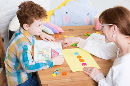 Therapy session with the therapist teaching the young boy alphabet Stock Photo