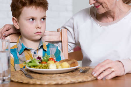 Irritated boy, sitting at a table with healthy lunch with vegetables