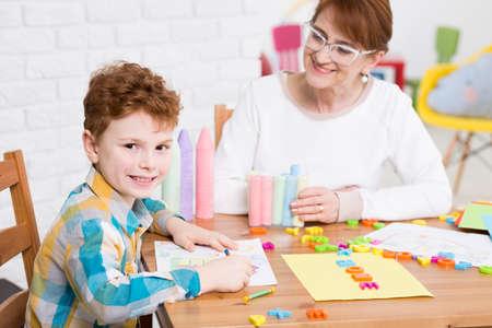 웃으면 소년과 그의 심리학자와 치료 센터 내부 스톡 콘텐츠