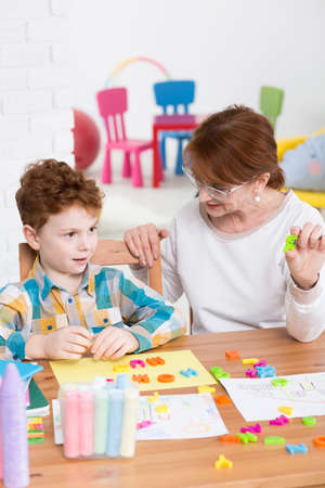 Young boy learning the alphabet with the teacher help