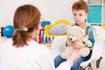 Roodharige, autistische jongen met teddybeer concentreerde zich op zijn therapeut Stockfoto - 61811072