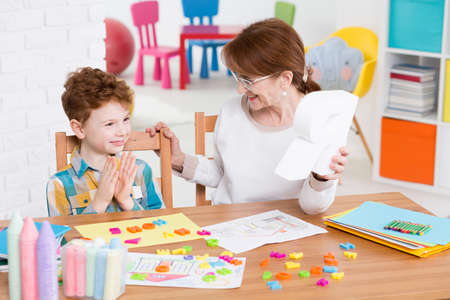 therapist: Red-haired boy satisfied with the alphabet learning with the speech therapist Stock Photo