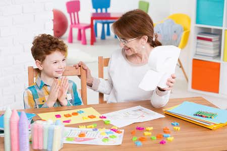 Rudowłosa chłopca zadowolony z nauki alfabetu z logopedą Zdjęcie Seryjne