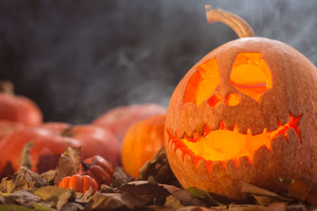 Closeup shot of a scary pumpkin face and a fog in the background