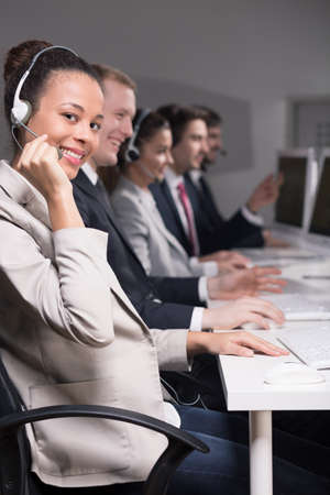 handsfree telephone: Row of telemarketers with headsets at work Stock Photo