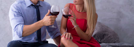 temptation: Woman in a red dress and a man in a blue shirt are toasting with glasses of wine