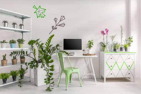 Wit interieur versierd met potplanten, eenvoudig bureau, stoel, computer en commode