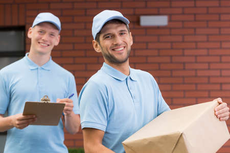 smiled: Two post men standing in front of the house with the delivery