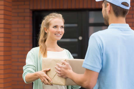 deliverer: Smiled, blonde woman receiving the delivery from the post man