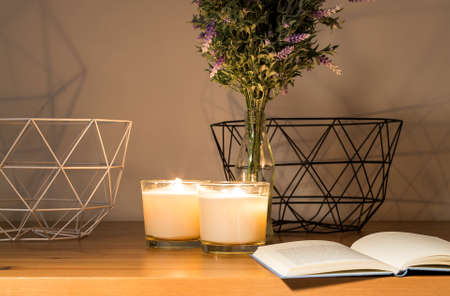 atmospheres: Tabletop with open book, candles, flowers in the glass bottle and shadows on the wall