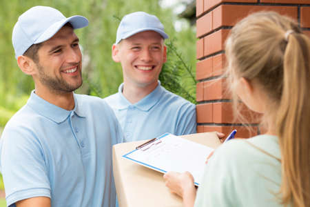 Smiled delivery men looking at the young woman signing the delivery sheet