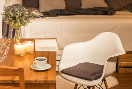 amenities: Cosy bedroom interior with wooden table with candles and cup of coffee on, minimalistic chair and sofa full of cushions