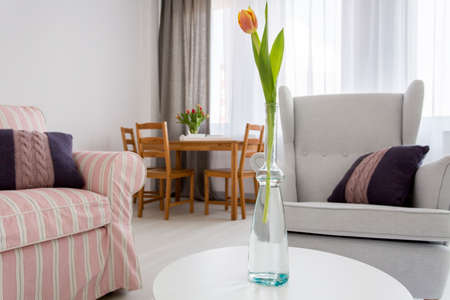 upholstered: Spacious interior with upholstered sofa and armchair, wooden table and chairs