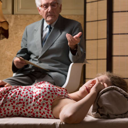 Elder psychotherapist looking at young woman lying on a couch
