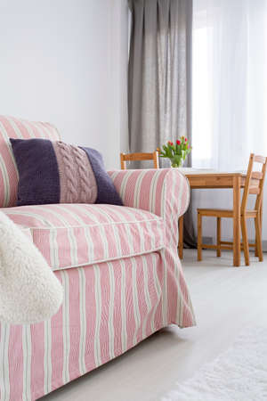 upholstered: Upholstered pattern sofa, in the background wooden table and chairs