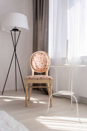upholstered: Light living room with beautiful upholstered chair, small table and floor lamp Stock Photo