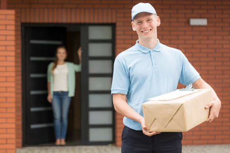 smiled: Smiled courier with a delivery with the young woman standing at front door Stock Photo