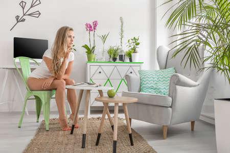 Jonge vrouw zittend op een stoel in een nieuw design, licht vlak onder versierd met groene kamerplanten