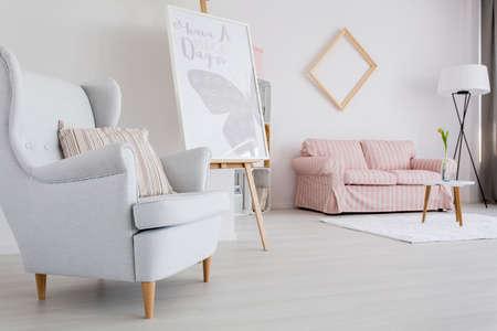 Ruime vrouwelijk woonkamer met licht leunstoel en gestoffeerde sofa