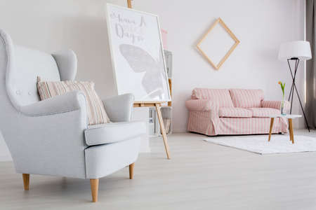 living room sofa: Spacious feminine living room with light armchair and upholstered sofa Stock Photo