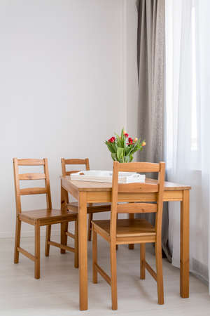 dining table and chairs: Wooden dining table and chairs standing in light interior