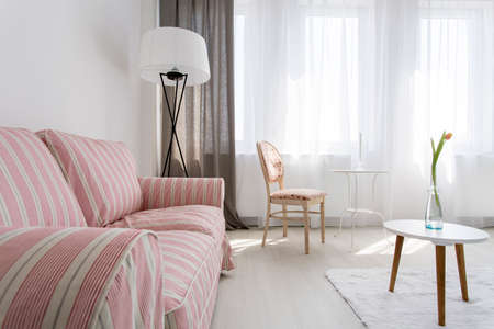 small table: Light and spacious home interior with upholstered pattern sofa, small table, stylish chair and floor lamp